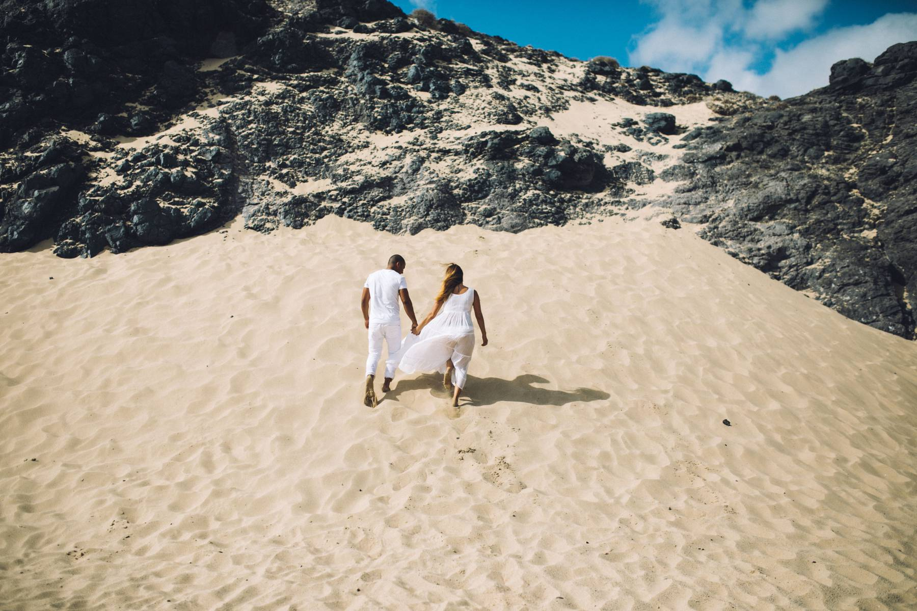 Bride and groom hike on sand dune
